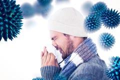 Samengesteld beeld van de knappe mens op de wintermanier die zijn neus blazen royalty-vrije stock foto's
