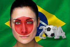 Samengesteld beeld van de voetbalventilator van Japan in gezichtsverf Stock Fotografie
