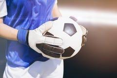 Samengesteld beeld van dichte die omhooggaand van een voetbal door sportvrouw wordt gehouden stock afbeeldingen