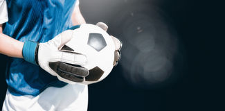 Samengesteld beeld van dichte die omhooggaand van een voetbal door sportvrouw wordt gehouden stock fotografie