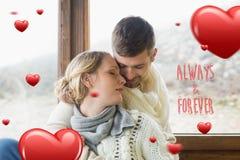 Samengesteld beeld van dichte omhooggaand van een houdend van jong paar in de winterkleding Stock Foto's