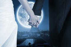 Samengesteld beeld van dichte omhooggaand van leuke jonge jonggehuwden die hun handen houden Stock Afbeelding