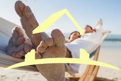 Samengesteld beeld van dichte omhooggaand van zandige voeten van paar in een hangmat Stock Fotografie