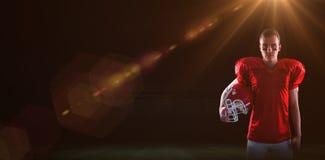 Samengesteld beeld van een ernstige Amerikaanse voetbalster die camera bekijken Stock Afbeelding