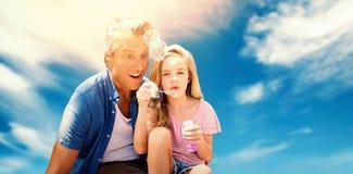 Samengesteld beeld van een kleine meisjes blazende bellen met haar vader royalty-vrije stock afbeelding
