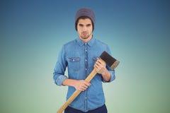 Samengesteld beeld van ernstige hipster die de gebreide bijl van de hoedenholding dragen Royalty-vrije Stock Foto