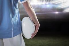 Samengesteld beeld van ernstige rugbyspeler met gekruiste wapens Stock Foto's