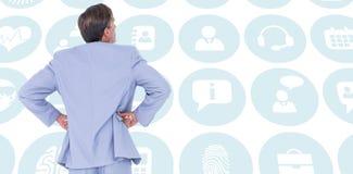 Samengesteld beeld van ernstige zakenman met handen op heupen stock fotografie