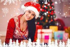 Samengesteld beeld van feestelijk brunette die haar lijst schrijven Stock Foto's
