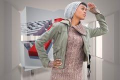 Samengesteld beeld van geconcentreerd jong model in de winterkleren die rond haar letten op Stock Foto