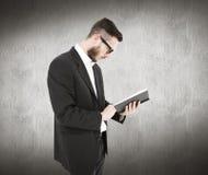 Samengesteld beeld van geeky jonge mensenlezing van zwart boek Stock Foto
