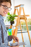 Samengesteld beeld van geeky zakenman die zijn tabletpc met behulp van stock foto's