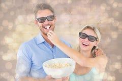 Samengesteld beeld van gelukkig jong paar die 3d glazen dragen die popcorn eten Stock Afbeeldingen