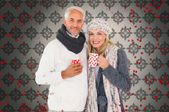 Samengesteld beeld van gelukkig paar in de holdingsmokken van de de wintermanier Stock Foto
