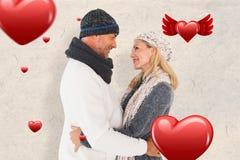 Samengesteld beeld van gelukkig paar in de wintermanier het omhelzen Stock Afbeeldingen
