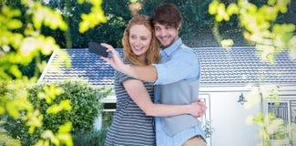 Samengesteld beeld van gelukkig paar die een selfie vastspijkeren stock foto's