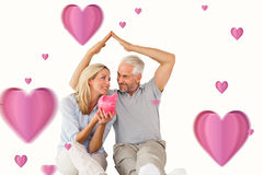 Samengesteld beeld van gelukkig paar zitting en het beschutten spaarvarken Royalty-vrije Stock Fotografie