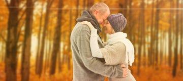 Samengesteld beeld van gelukkig rijp paar in de winterkleren het omhelzen stock foto's