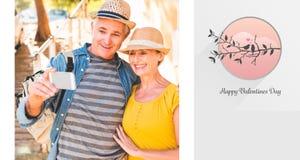 Samengesteld beeld van gelukkig rijp paar die een selfie samen in de stad nemen Stock Afbeeldingen