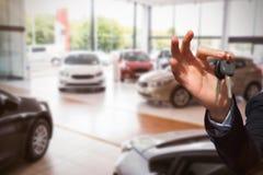 Samengesteld beeld van gelukkige de autosleutels van de verkopersholding Stock Foto's