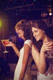Samengesteld beeld van gelukkige jonge vrouwen die rode cocktail hebben Stock Afbeeldingen