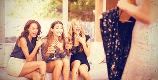 Samengesteld beeld van gelukkige vrouwen die hun vriendenkleding bekijken stock afbeeldingen