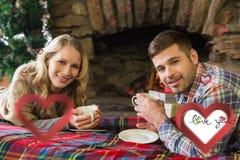 Samengesteld beeld van glimlachend paar met theekoppen voor aangestoken open haard Stock Afbeeldingen
