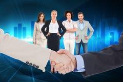Samengesteld beeld van glimlachende bedrijfsmensen die handen schudden terwijl het bekijken de camera Royalty-vrije Stock Foto