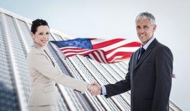 Samengesteld beeld van glimlachende bedrijfsmensen die handen schudden terwijl het bekijken de camera Stock Fotografie