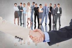 Samengesteld beeld van glimlachende bedrijfsmensen die handen schudden terwijl het bekijken de camera Royalty-vrije Stock Foto's