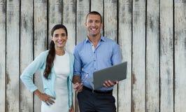 Samengesteld beeld van glimlachende bedrijfsmensen die laptop met behulp van Stock Foto's