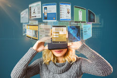 Samengesteld beeld van glimlachende blonde vrouw die virtuele 3d werkelijkheidshoofdtelefoon met behulp van Royalty-vrije Stock Foto's