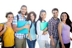 Samengesteld beeld van glimlachende groep studenten die zich op een rij bevinden royalty-vrije stock afbeeldingen