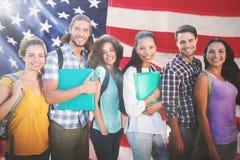 Samengesteld beeld van glimlachende groep studenten die zich op een rij bevinden royalty-vrije stock foto's