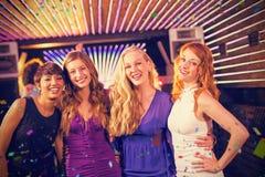 Samengesteld beeld van glimlachende vrouwelijke vrienden die zich in bar verenigen stock fotografie