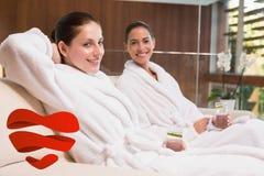 Samengesteld beeld van glimlachende vrouwen in badjassen die op laag zitten Stock Afbeeldingen