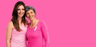 Samengesteld beeld van glimlachende vrouwen in roze uitrustingen die voor de voorlichting van borstkanker stellen royalty-vrije stock foto's