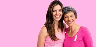Samengesteld beeld van glimlachende vrouwen in roze uitrustingen die voor de voorlichting van borstkanker stellen royalty-vrije stock afbeeldingen