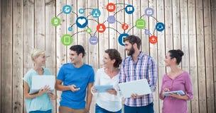 Samengesteld beeld van groep jonge collega's die laptop en tablet gebruiken stock foto