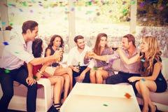 Samengesteld beeld van groep vrienden die en dranken spreken hebben stock afbeeldingen
