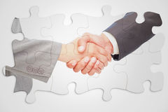 Samengesteld beeld van handdruk tussen twee bedrijfsmensen Stock Afbeeldingen