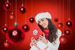 Samengesteld beeld van het glimlachen van de donkerbruine giften van holdingskerstmis Stock Foto