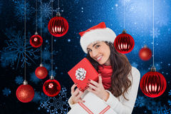 Samengesteld beeld van het glimlachen van de donkerbruine giften van holdingskerstmis Stock Fotografie