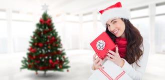 Samengesteld beeld van het glimlachen van de donkerbruine giften van holdingskerstmis Stock Foto's