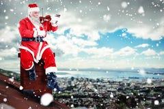 Samengesteld beeld van het glimlachen van het spelen van de Kerstman viool op stoel royalty-vrije stock fotografie
