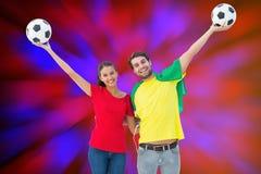 Samengesteld beeld van het paar die van de voetbalventilator en bij camera toejuichen glimlachen royalty-vrije stock afbeeldingen