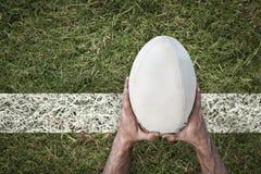 Samengesteld beeld van het rugbybal van de mensenholding Stock Afbeeldingen