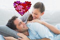 Samengesteld beeld van het vrolijke paar ontspannen op hun bank die bij elkaar glimlachen Stock Foto's