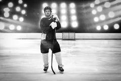 Samengesteld beeld van hockeyspeler met hockeystok die zich op piste bevinden stock fotografie