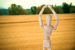 Samengesteld beeld van houten 3d beeldje opgeheven status met handen Stock Afbeeldingen